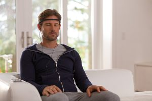 Man sitting and meditating while wearing a Gaiam brain sensing headband