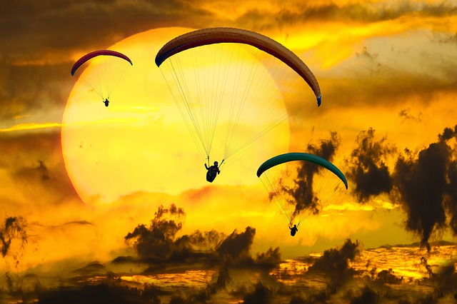 gliding, paragliding, and flying through the air to a sunset