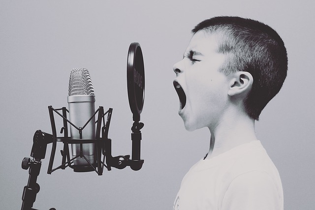 A child shouting at a studio microphone
